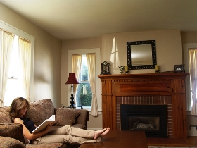 woman sitting on sofa reading beside traditional fireplace